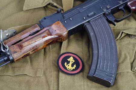 communism: AK47 with Soviet Army Marines shoulder patch on khaki uniform background