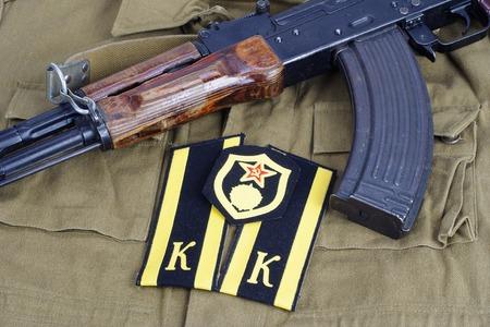 troops: AK47 with Soviet Army Cadet shoulder mark  and Soviet Army chemical troops shoulder patch on khaki uniform background Stock Photo