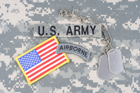 KIEV, UKRAINE - August 21, 2015. US ARMY airborne tab, flag patch,  with dog tag on camouflage uniform