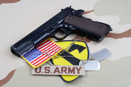45 ammo: KIEV, UKRAINE - May 18, 2015. US ARMY 1st Cavalry Division patch with dog tags, colt government M1911 on desert uniform