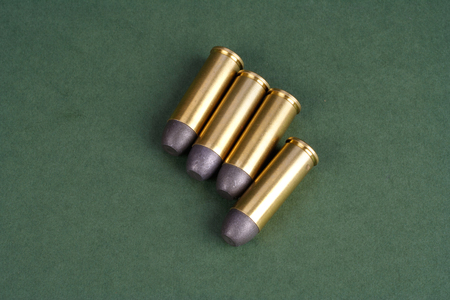 45 gun: The Wild West period Revolver cartridges dating to 1872 on green background Stock Photo