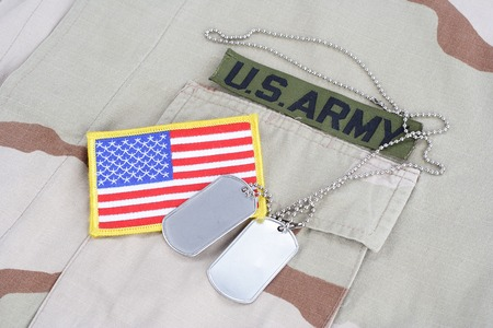 us army: KIEV, UKRAINE - June 14, 2015. US ARMY branch tape with dog tags and flag patch on desert camouflage uniform