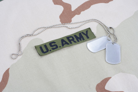 us army: KIEV, UKRAINE - June 14, 2015. US ARMY branch tape with dog tags on desert camouflage uniform