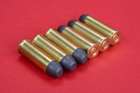 The .45 Revolver cartridges dating to 1872 on red background Stock Photo