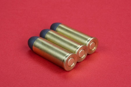 45 gun: The .45 Revolver cartridges dating to 1872 on red background Stock Photo