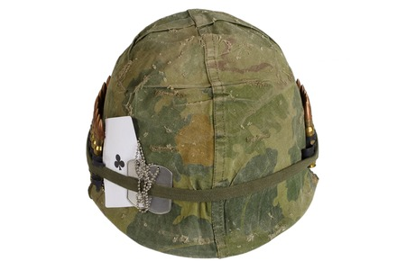 ace of clubs: US Army helmet Vietnam war period with camouflage cover and ammo belt, dog tag and amulet - ace of clubs playing card Stock Photo
