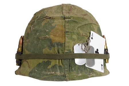 silver state: US Army helmet Vietnam war period with camouflage cover and ammo belt, dog tag and amulet - ace of clubs playing card Stock Photo