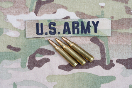 us army: KIEV, UKRAINE - September 5, 2015. US ARMY branch tape and 5.56 mm rounds on camouflage uniform