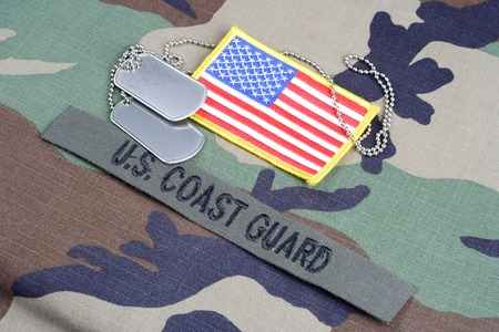 coast guard: KIEV, UKRAINE - June 6, 2015. US COAST GUARD branch tape, flag patch and dog tags on woodland camouflage uniform