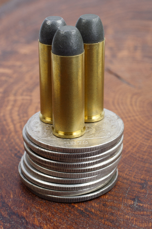Revolver cartridges and Silver Dollars Wild West period on wooden background Stock Photo