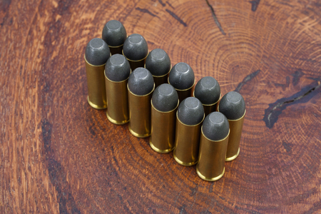 Revolver cartridges .45 Cal Wild West period on wooden background Stock Photo