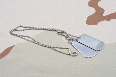 Dog tags and USA flag patch on desert camouflage uniform