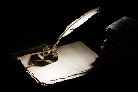 Old fountain pen, books and inkwell on a black background
