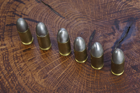 The 9mm caliber cartridges on wooden background