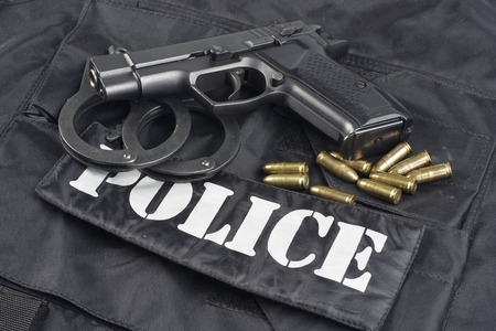 Police concept - handgun on black uniform background