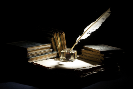 Vintage concept. Old fountain pen, books and inkwell on a black background Stock Photo