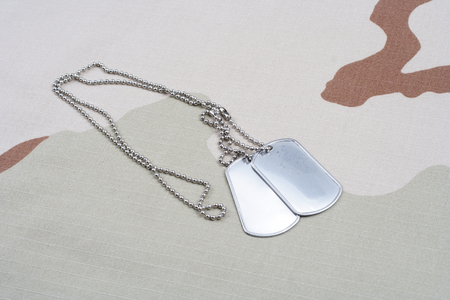 Dog tags on desert camouflage uniform