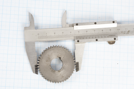 gears and caliper on graph paper background Stock fotó