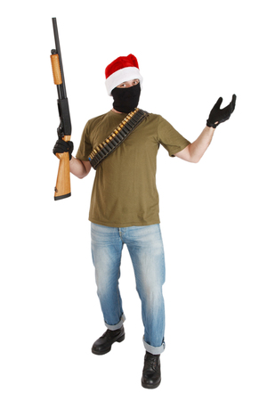 robber in black mask and cap of Santa Claus with shotgun isolated Фото со стока