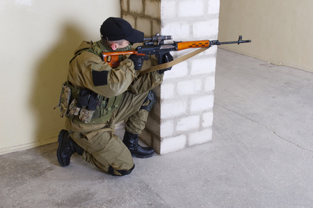 guerillas sniper with sniper rifle inside the building Stock Photo