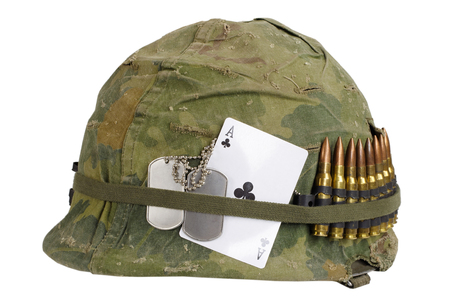 US Army helmet Vietnam war period with camouflage cover and ammo belt, dog tag and amulet - ace of clubs playing card Stock Photo