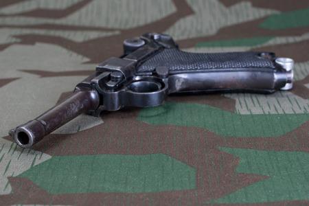 World War II period german army handgun with german award Iron Cross 1914 on camouflaged background