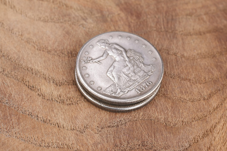 antique silver dollar on wooden background