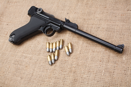 World War I period german army handgun with cartridges on canvas background Reklamní fotografie