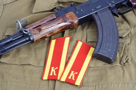 AK47 with Soviet Army Cadet shoulder mark on khaki uniform background