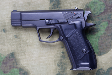 modern handgun on camouflage background