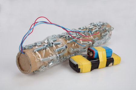 Pipe Bomb with cell phone firing device on grey background