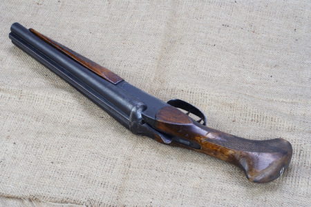 Illegal weapon - sawn off shotgun on canvas background
