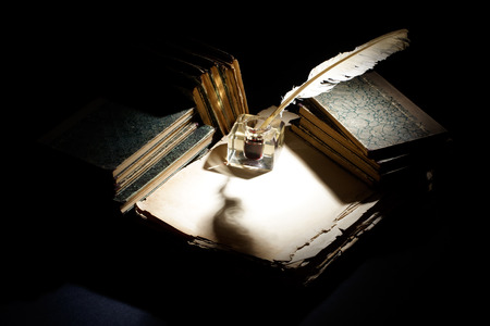 Vintage background with old ink bottle, books, papers and quill background
