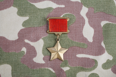 The Gold Star medal is a special insignia that identifies recipients of the title Hero in the Soviet Union on Soviet camouflage uniform background