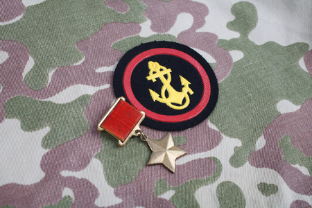 The Gold Star medal is a special insignia that identifies recipients of the title Hero in the Soviet Union on Soviet and Marines shoulder patch on camouflage uniform background