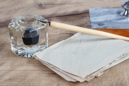 Vintage concept - Old fountain pen and inkwell with old letters on a wooden background