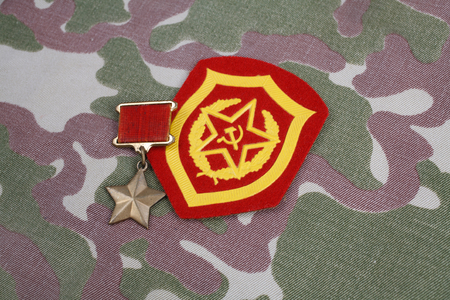 The Gold Star medal is a special insignia that identifies recipients of the title Hero in the Soviet Union on Soviet and Mechanized infantry shoulder patch on camouflage uniform background