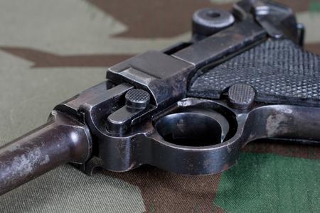 World War II period german army handgun with german award Iron Cross 1914 on camouflaged uniform background