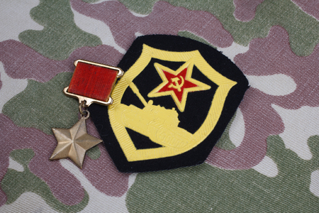 The Gold Star medal is a special insignia that identifies recipients of the title Hero in the Soviet Union on Soviet and Tank Corps shoulder patch on camouflage uniform background Editorial