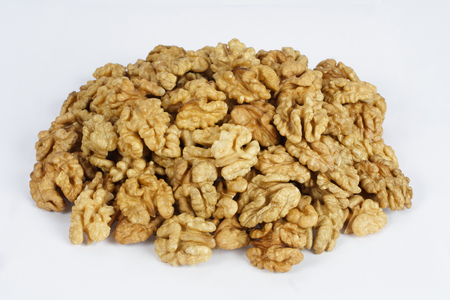 The pile of English walnuts kernels on white
