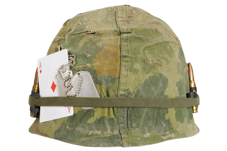 US Army helmet Vietnam war period with camouflage cover and ammo belt, dog tag and amulet - playing card ace of diamonds isolated on white background