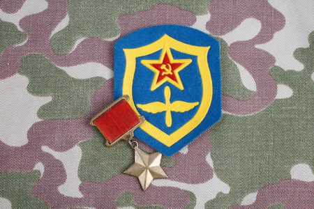 The Gold Star medal is a special insignia that identifies recipients of the title Hero in the Soviet Union on Soviet and Air Force shoulder patch on camouflage uniform background