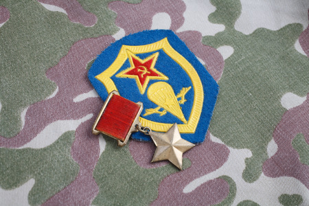 The Gold Star medal is a special insignia that identifies recipients of the title Hero in the Soviet Union on Soviet and Airborne forces shoulder patch on camouflage uniform background Editorial