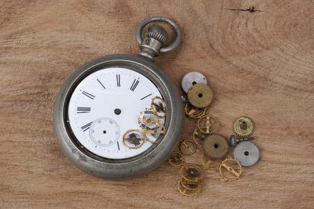 broken vintage pocket watch on wooden background