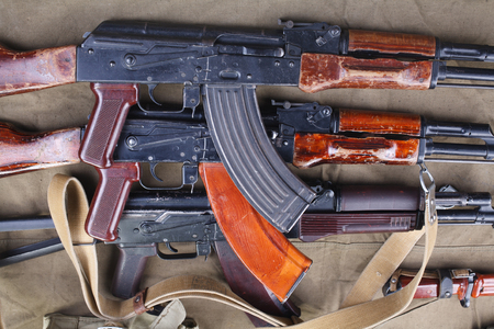 three ak 47 on canvas with ammunitions on canvasbackground