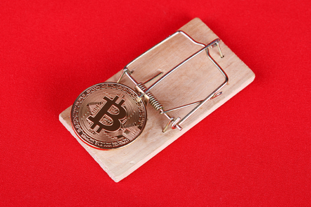mousetrap with bitcoin on red background Foto de archivo