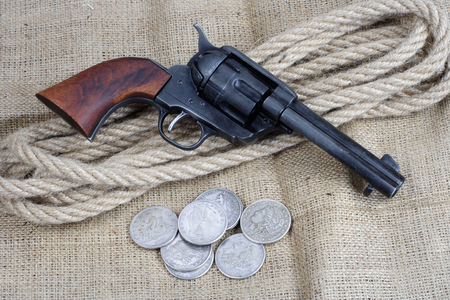 wild west revolver - colt single action army with silver dollars on canvas background