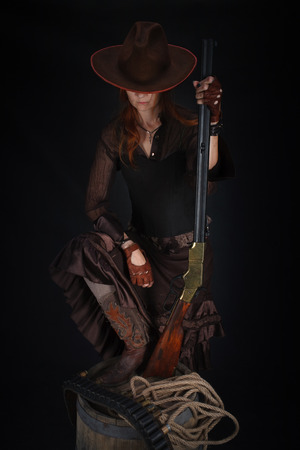Chica del salvaje oeste con rifle sobre fondo negro