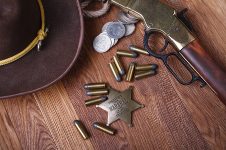 Wild west rifle, ammunition and sheriff badge on wooden table Imagens