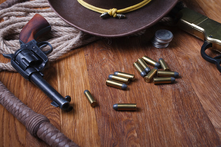 Wild west guns, ammunition and silver dollars on wooden table Stock Photo